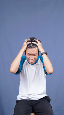 asian man stress gesture and expression holding head and hair with isolated blue background Banque d'images