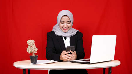Asian business woman see hand phone happy gesture in workspace islolated