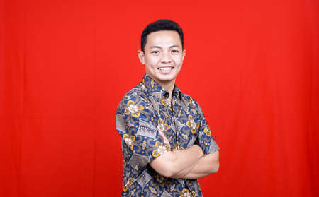 asian man stylish with batik clothes in studio isolated with red background