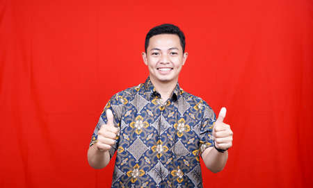 asian man OK expression with batik clothes in studio isolated with red background
