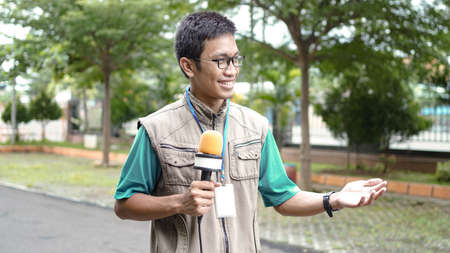 asian male journalist wear vest and ready for news