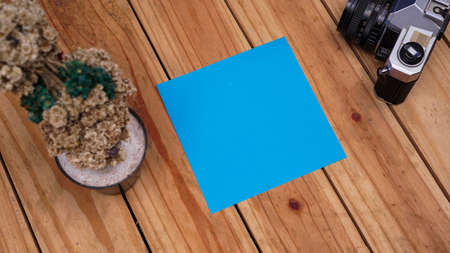 blank blue paper for quotes with edelweis and old camera on top wood table