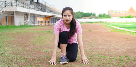 asian woman athlete getting ready to start running on track