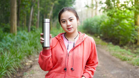 Asian women drinking water after exercise on green nature forest background