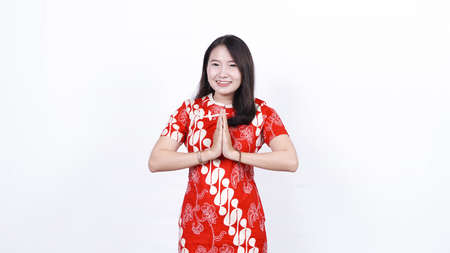 Asian Chinese woman in a cheongsam dress with congratulations gesture. Happy Chinese New Year