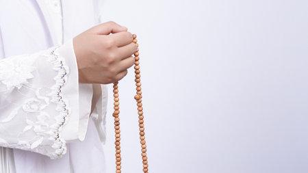 Asian muslim woman wearing prayer beads pray with tasbih in white background