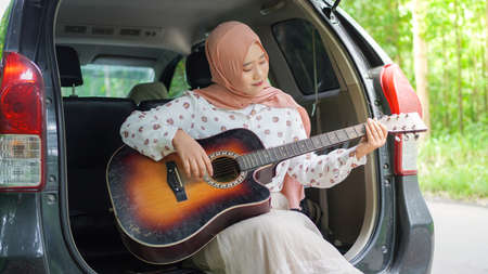 asian woman tavelling wearing hijab playing guitar with a car Banque d'images