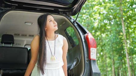 portrait of happy asian woman travelling in back car