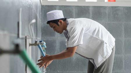 亚洲穆斯林沐浴粉的画象在清真寺祈祷之前