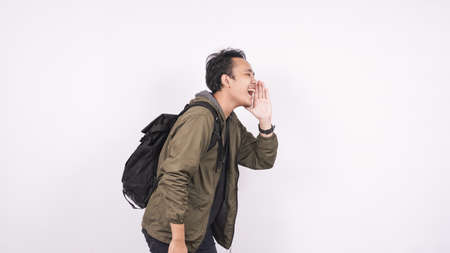Young student man wearing a bag shouting and yelling isolated on white backgroud
