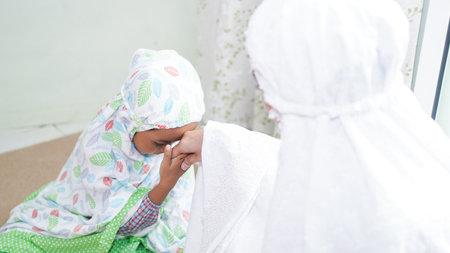 一个由父母和孩子组成的穆斯林家庭在祷告期间进行问候运动