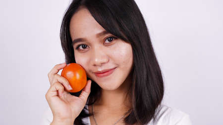 Close up beautiful asian women with a tomato isolated on white background