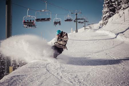 snowboarder sprays snow in kicking horse ski resort