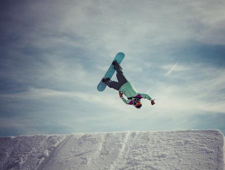 BACKFLIP: snowboarder jumping a superman backflip in Laax, Switzerland. Stock Photo