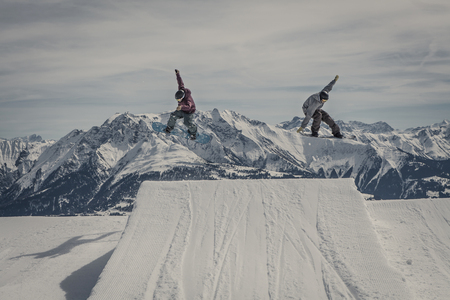 tweak: snowboarder jumping synchronous @ Laax, Switzerland with amazing mountain view Stock Photo