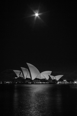 nightshot: nightshot of syney opera and full moon with water in front Stock Photo