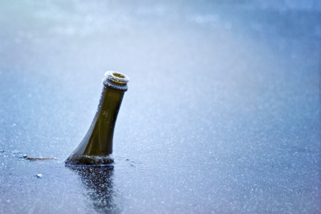 bottle of sparkling wine frozen in ice in lake on new years day