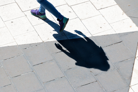shadow of person walking in a square