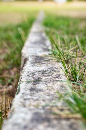 Grenzlinie im Rasen aus Kalkstein Standard-Bild