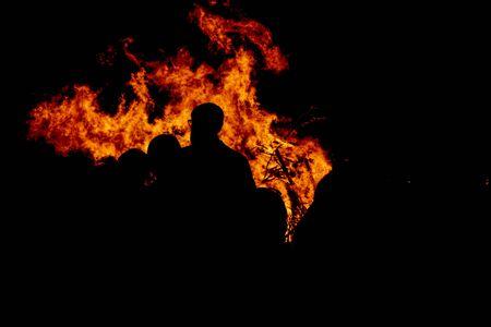 People watching fire burning at night Stock fotó