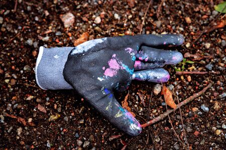 abandoned rubber glove with paint on the ground