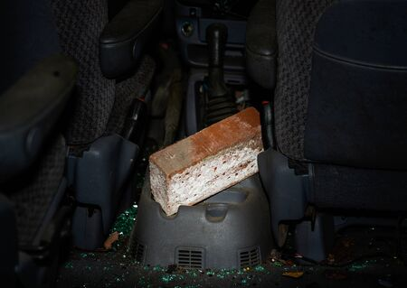 Brick in abandoned and vandalized car