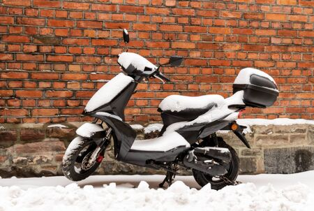 Abandoned moped scooter in snow in winter