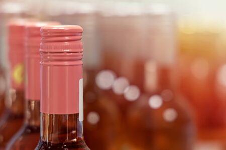bottles of rose wine on shelf Imagens