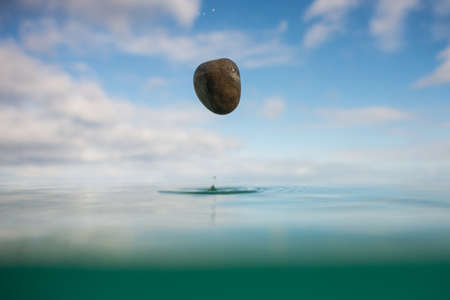 unwind: Rock falling into the ocean Stock Photo