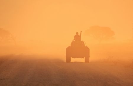 Tractor driver and sunset dust of gold photo
