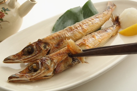 Eating grilled dried Japanese silver whiting fish with chopsticks