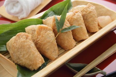 いなり寿司に包まれた酒と揚げ豆腐和食 写真素材