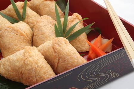 いなり寿司に包まれた、和食のランチ ボックス入り揚げ豆腐