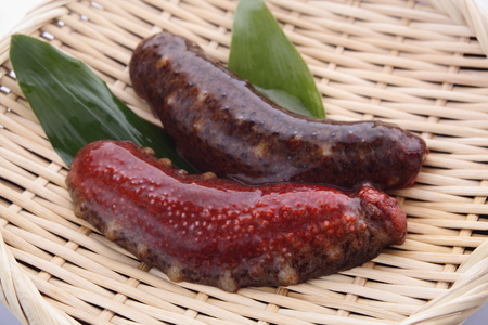 Two raw red sea cucumber on bamboo colander