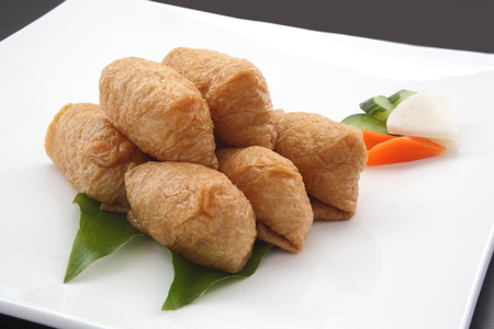 Inari Sushi; Vinegar-Ed Rice Wrapped in Fried Tofu with Japanese Pickles on White Plate, Japanese Food Stock Photo