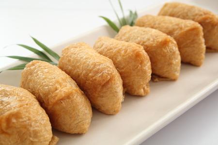いなり寿司。米酢 Ed に包まれた白い背景、日本食品の揚げ豆腐 写真素材