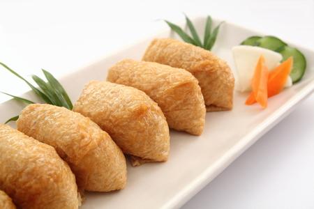 いなり寿司。白い背景に、和食の漬物と揚げ豆腐に包まれた米酢 Ed
