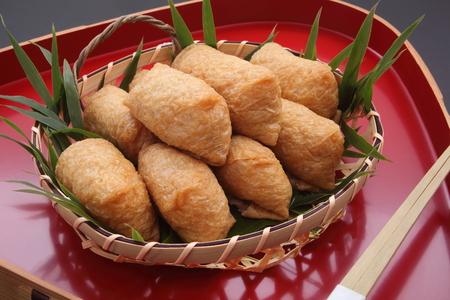いなり寿司。酢 Ed 米に包まれた漆塗りトレー、和食の竹かご入り揚げ豆腐