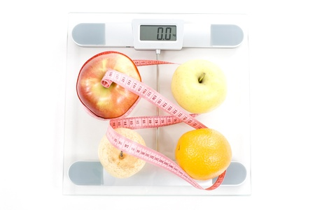 Fruits surrounded by a measuring tape on a glass bathroom scale. Blank display.  photo