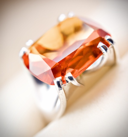 signet: retro old silver ring with orange gem in box isolated on a white  Stock Photo