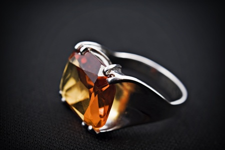 signet: retro old silver ring with orange gem on black background