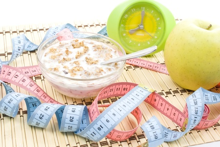 Apple and muesli tighten with measure tape isolated on white  photo