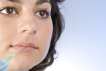 recieving: Beautiful woman recieving a botox injection in her lip