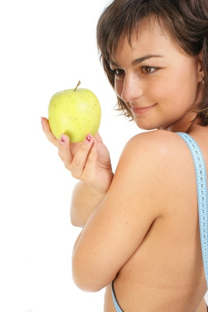 Young girl with measuring tape around slim beautiful waist and holding an apple Stock Photo - 12267062
