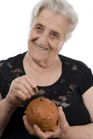 Elderly woman depositing money in piggy bank isolated over white background photo