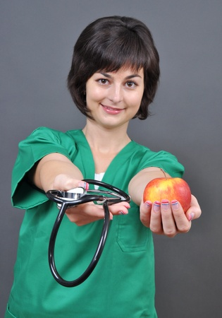 Attractive lady doctor with stethoscope and fresh apple on gray background  Stock Photo - 12266719