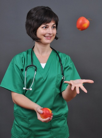 Attractive lady doctor and fresh apples on gray background  photo
