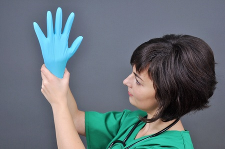 gynecologist: Doctor putting on blue sterilized medical glove for making operation