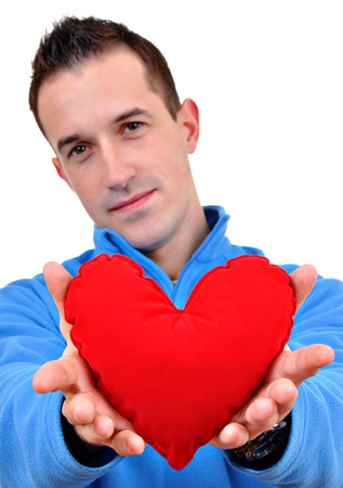 Young man holding heart in his hand. He is giving it somebody. Isolated on white. Stock Photo - 12267141
