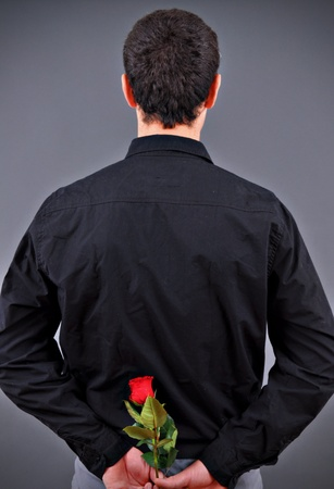 Man hiding a flower behind his back  photo